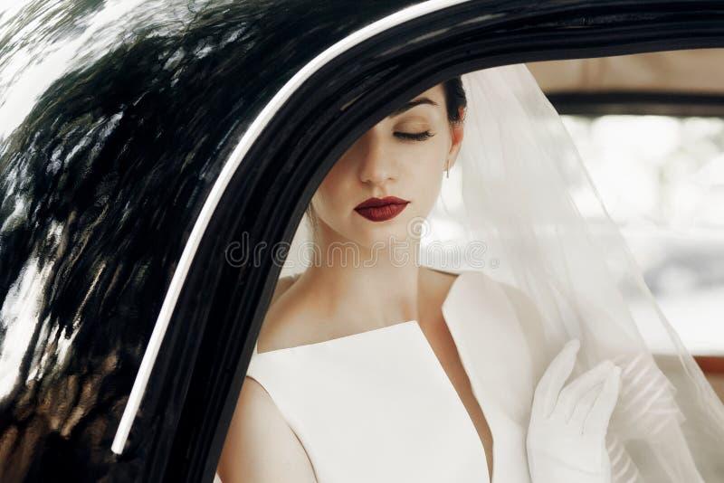 Herrliche elegante Braut, die im stilvollen Retro- schwarzen Auto, sittin aufwirft lizenzfreies stockbild