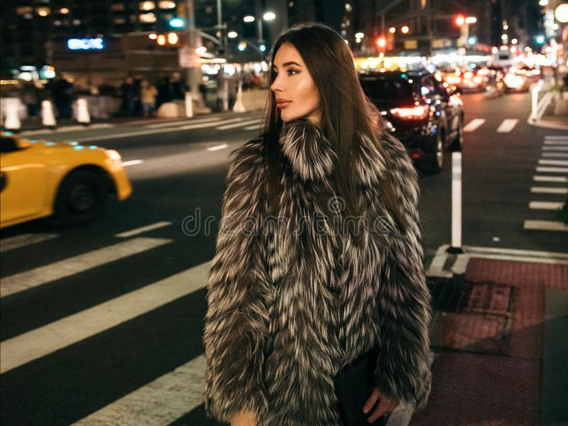 Herrliche elegante Frau, die auf die Nachtstadtstraße trägt gefälschte Pelzjacke und hält die Tasche schaut zur Seite geht lizenzfreie stockbilder