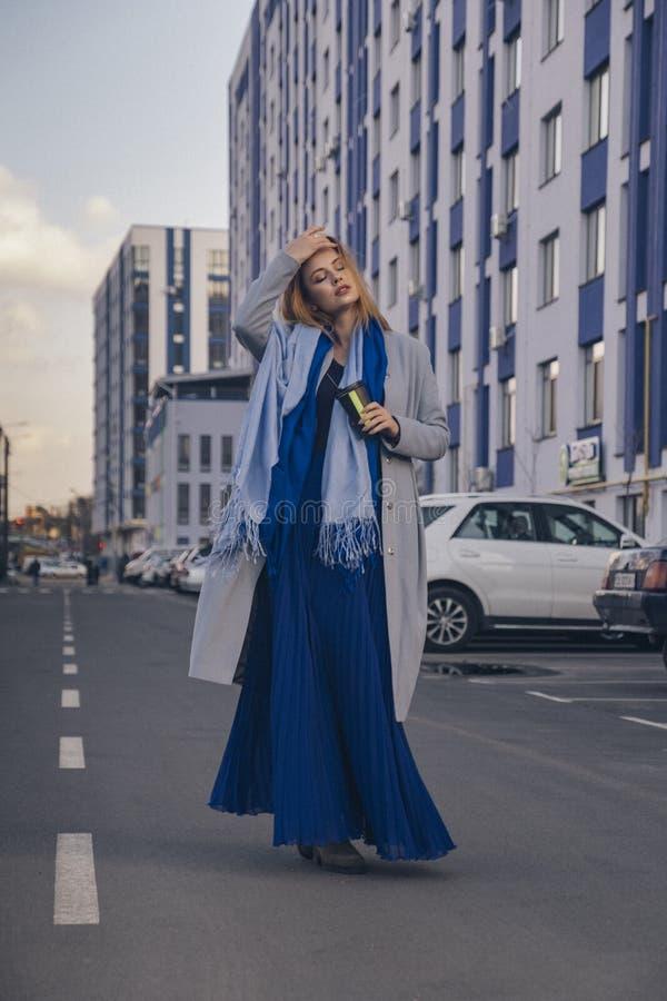 Herrliche europäische Frau im warmen Mantel und im Kleid auf einem Weg im Park nahe Fluss Windiges Wetter Ihre Kleidung fliegt in lizenzfreie stockfotos