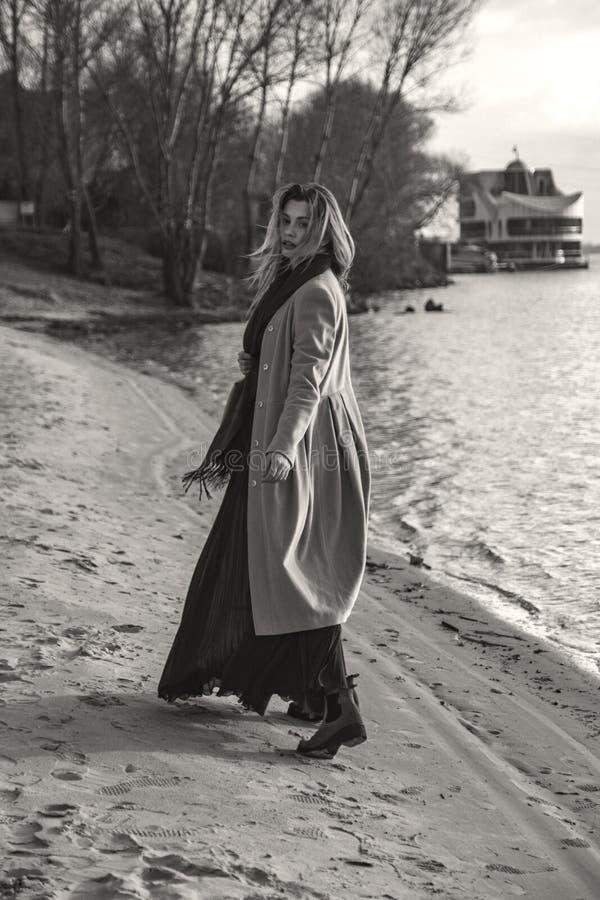 Herrliche europäische Frau im warmen Mantel und im Kleid auf einem Weg im Park nahe Fluss Windiges Wetter Ihre Kleidung fliegt in stockfotografie