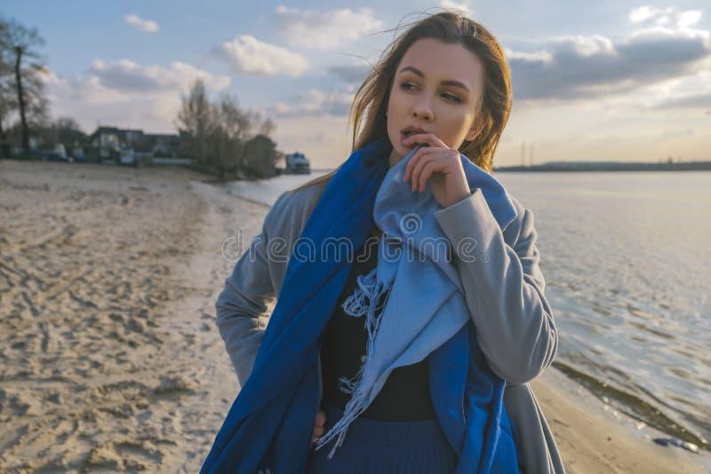 Herrliche europäische Frau im warmen Mantel und im Kleid auf einem Weg im Park nahe Fluss Windiges Wetter Ihre Kleidung fliegt in lizenzfreies stockbild