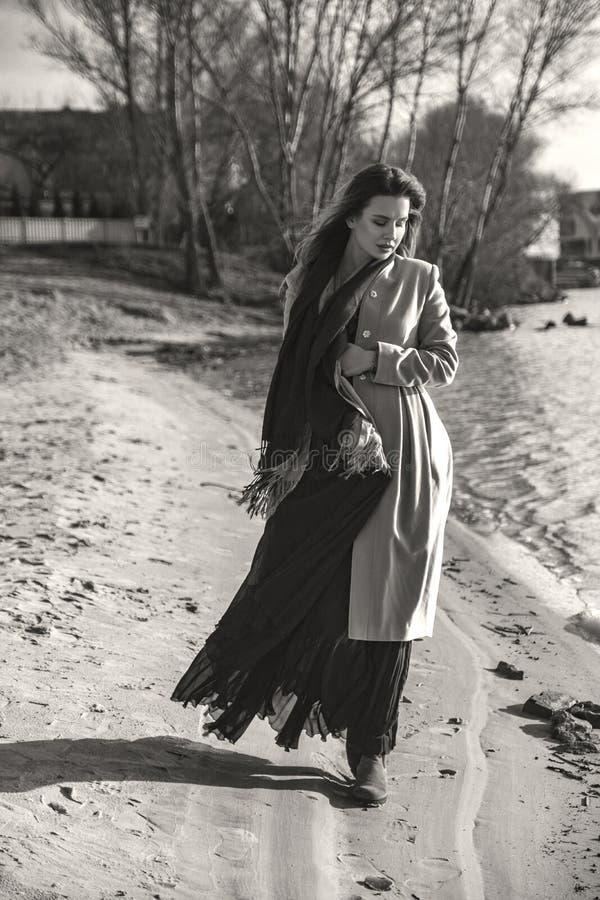 Herrliche europäische Frau im warmen Mantel und im Kleid auf einem Weg im Park nahe Fluss Windiges Wetter Ihre Kleidung fliegt in lizenzfreie stockbilder