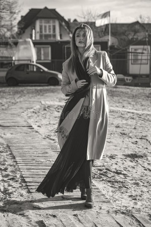 Herrliche europäische Frau im warmen Mantel und im Kleid auf einem Weg im Park nahe Fluss Windiges Wetter Ihre Kleidung fliegt in stockbild