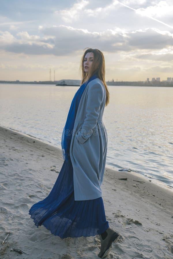 Herrliche europäische Frau im warmen Mantel und im Kleid auf einem Weg im Park nahe Fluss Windiges Wetter Ihre Kleidung fliegt in stockbilder
