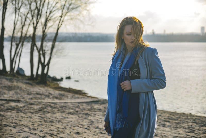 Herrliche europäische Frau im warmen Mantel und im Kleid auf einem Weg im Park nahe Fluss Windiges Wetter Ihre Kleidung fliegt in stockfotos