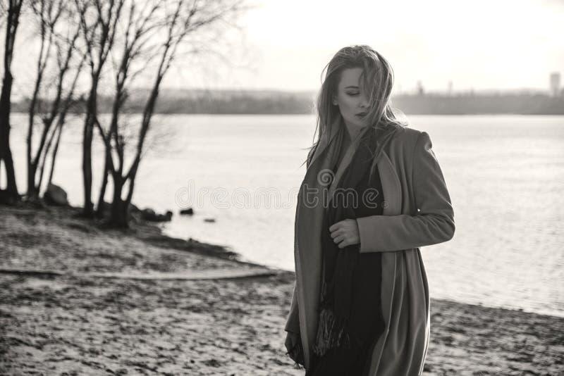 Herrliche europäische Frau im warmen Mantel und im Kleid auf einem Weg im Park nahe Fluss Windiges Wetter Ihre Kleidung fliegt in lizenzfreie stockfotografie