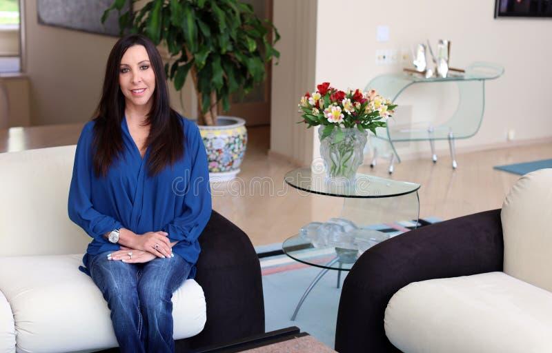 Herrliche Frau des dunklen Haares, die mit schönem blauem Hemd, Berufspsychologe in einem Art- DecoRaum lächelt stockfotografie