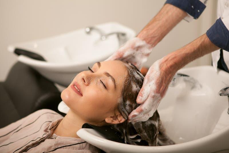 Herrliche Frau, die ihr Haar vom Friseur sich waschen lässt stockfoto