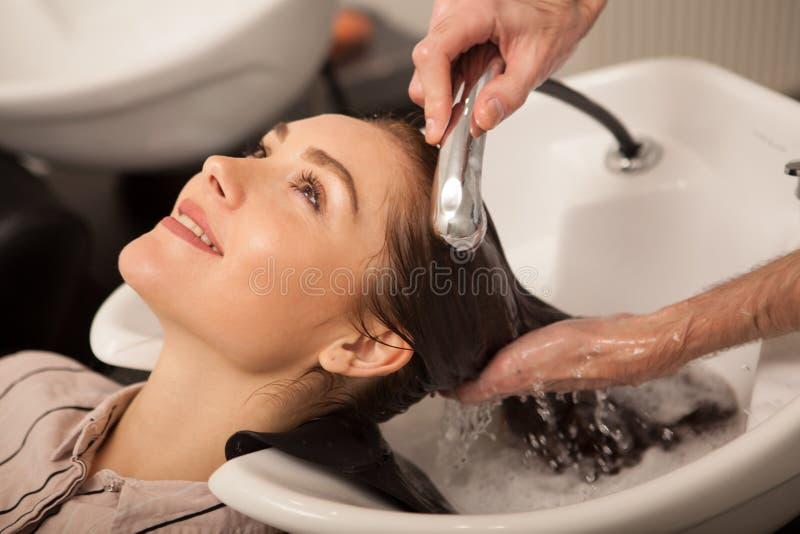 Herrliche Frau, die ihr Haar vom Friseur sich waschen lässt lizenzfreie stockfotos