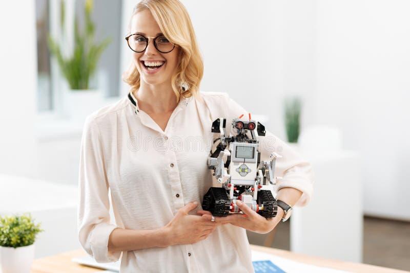 Herrliche Frau, die zuhause automatischen kleinen Roboter hält stockfotografie