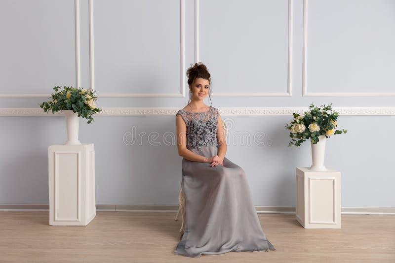 Herrliche Frau im transparenten Kleid sitzt auf Stuhl lizenzfreie stockbilder