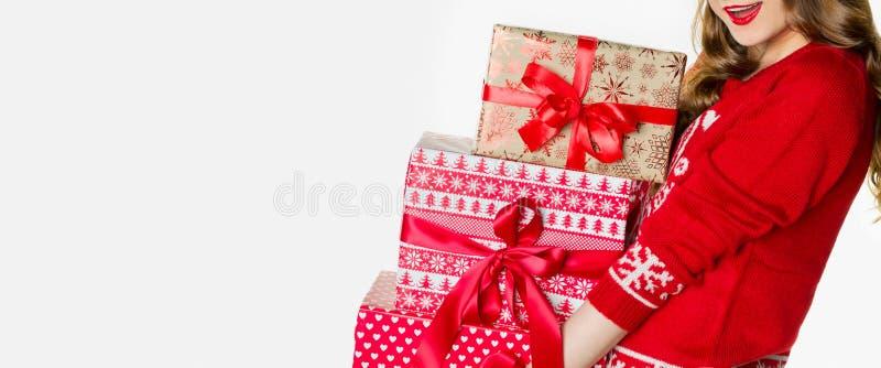 Herrliche Frau im Weihnachtspullover, der Lasten schweren Weihnachten hält, stellt sich, die Weihnachtsfahne dar, lokalisiert lizenzfreie stockbilder