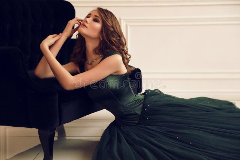 Herrliche Frau mit Make-up des dunklen Haares und des Abends im eleganten Kleid, das im Studio aufwirft lizenzfreies stockbild