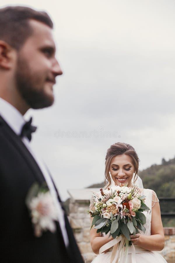 Herrliche glückliche Braut mit dem modernen Blumenstrauß, der stilvolles groo betrachtet stockfoto
