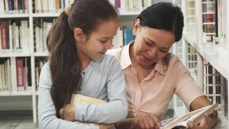 Herrliche glückliche reife Frau, die ein Buch zu ihrer kleinen Tochter liest stockfotografie
