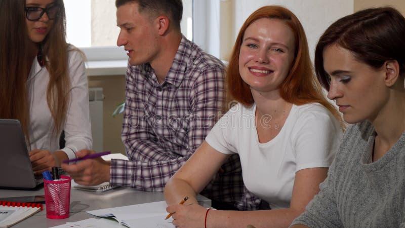 Herrliche glückliche Studentin, die zur Kamera, beim Studieren mit Freunden lächelt stockfotografie