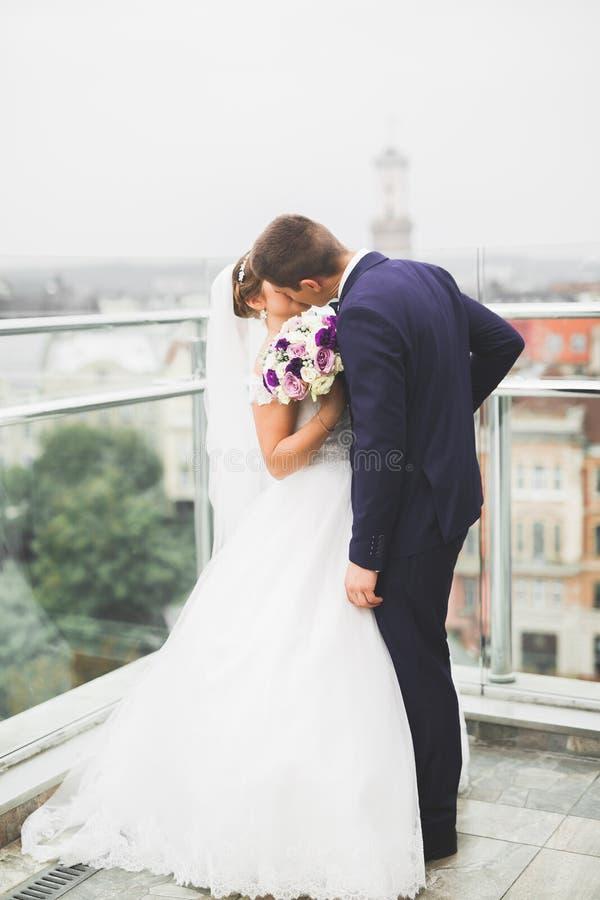 Herrliche Hochzeitspaare, die in der alten Stadt aufwerfen lizenzfreies stockfoto