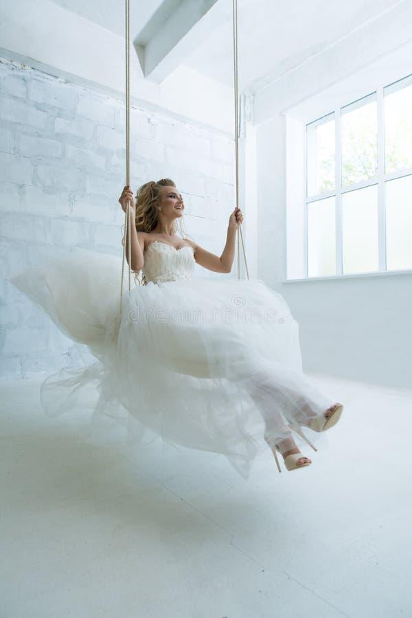 Herrliche junge Braut auf Schwingen im Studio stockfotografie
