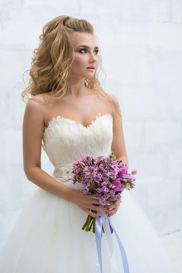 Herrliche junge Braut mit nettem Blumenstrauß im Studio lizenzfreies stockbild