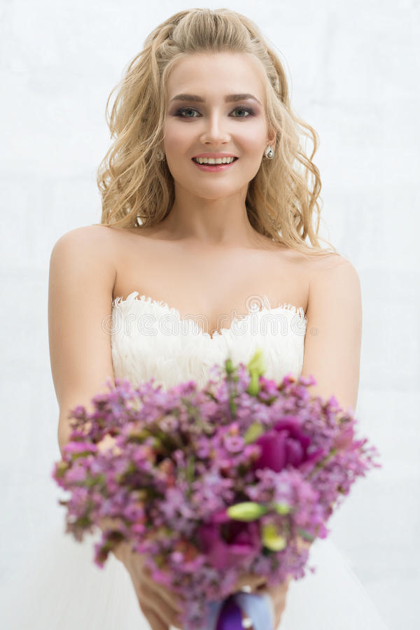 Herrliche junge Braut mit nettem Blumenstraußporträt stockbilder