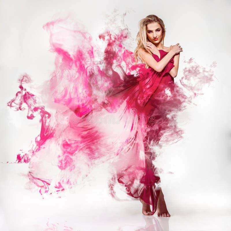 Herrliche junge erwachsene Blondine im rosa Kleid mit smo lizenzfreie stockfotografie