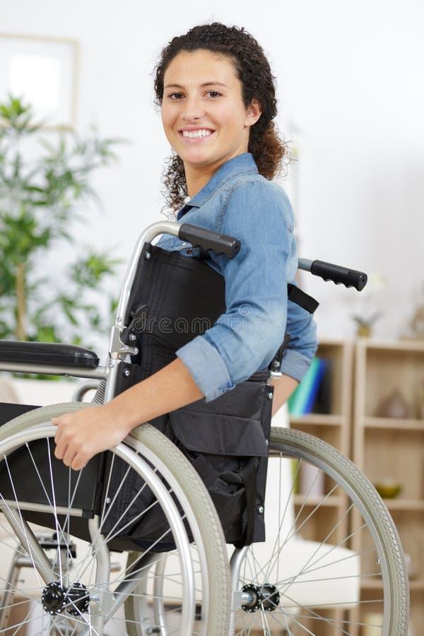 Herrliche junge Frau auf dem Rollstuhl, der sich zu Hause entspannt lizenzfreie stockfotos