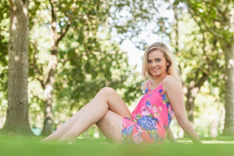 Herrliche junge Frau, die auf einem Rasen aufwirft stockbilder