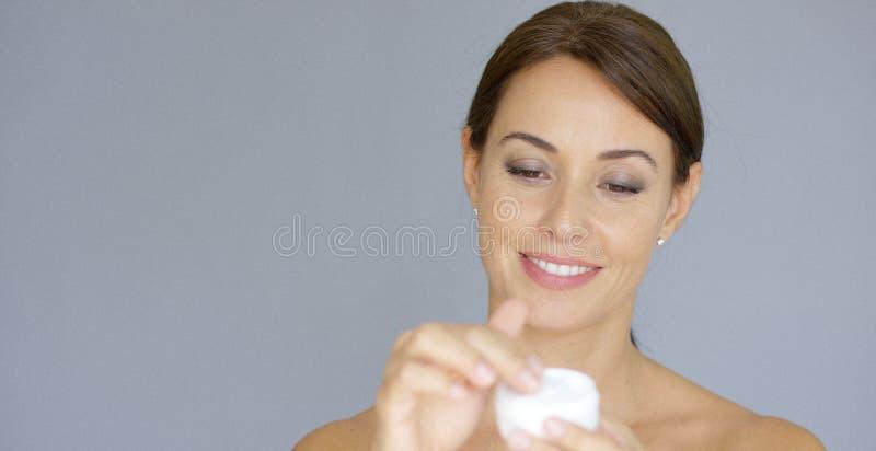 Herrliche junge Frau, die Gesichtscreme aufträgt stockbild