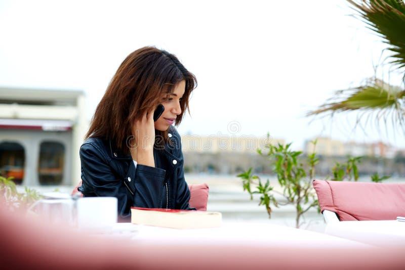 Herrliche junge Frau, die am Handy beim Sitzen im Straßencafé spricht stockbilder