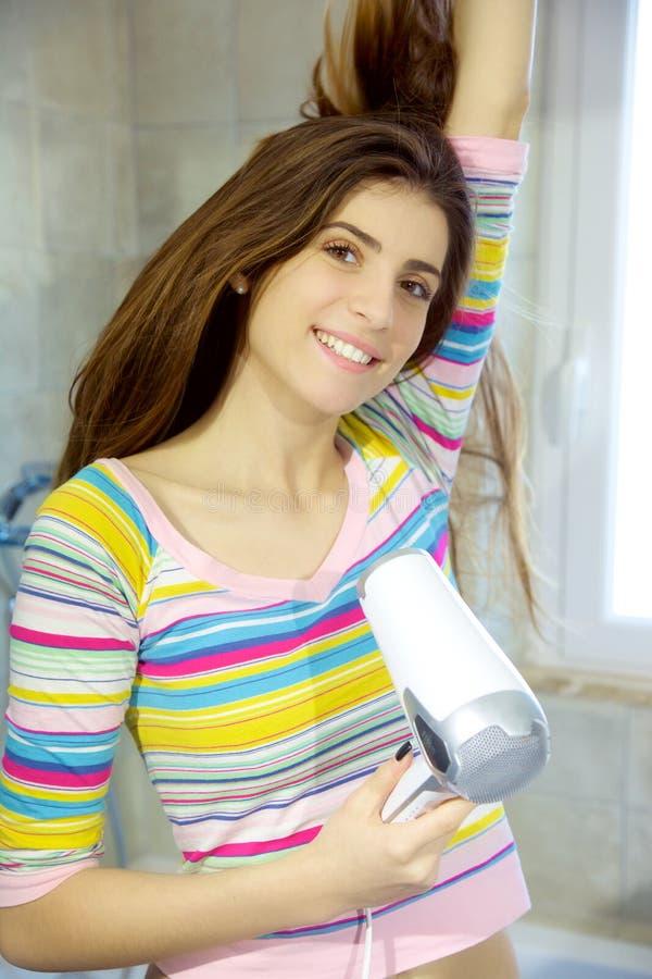 Herrliche junge Frau, die langes Haar im Badezimmer trocknet stockfotos