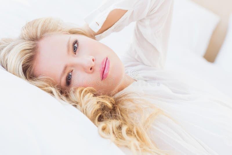 Herrliche junge Frau im weißen Hemd lächelnd an der Kamera, die auf Bett liegt lizenzfreie stockbilder