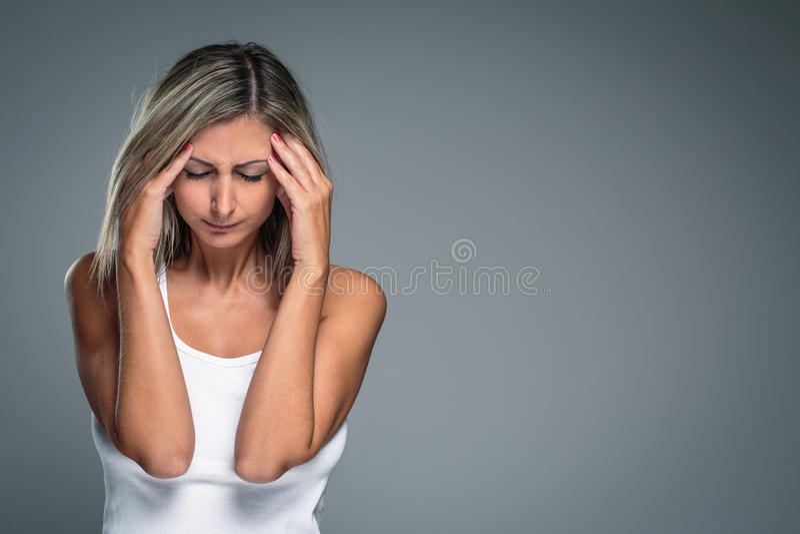 Herrliche junge Frau mit schweren Kopfschmerzen/Migräne/Krise stockbild