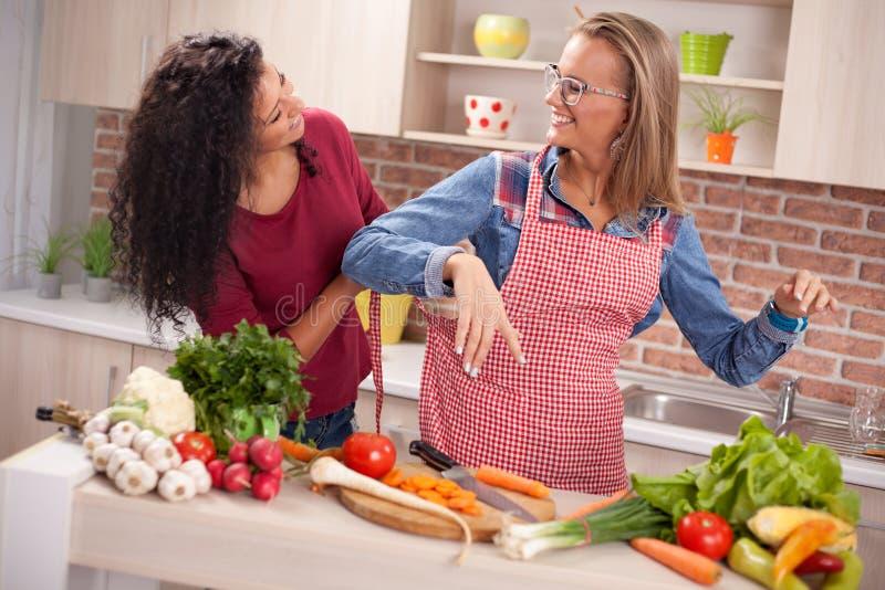 Herrliche junge Frauen, die Abendessen in einer Küche vorbereiten lizenzfreies stockfoto