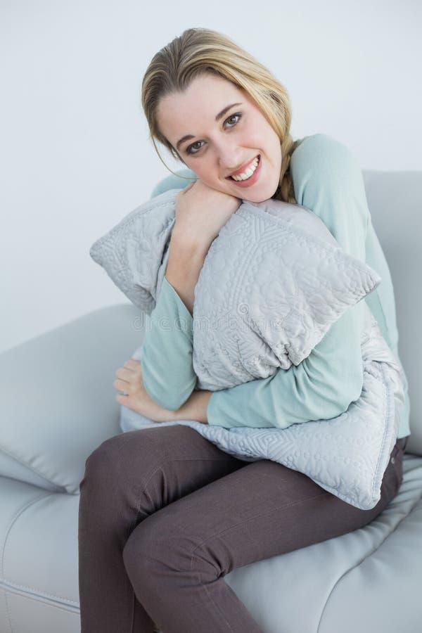 Herrliche lächelnde Frau, die mit dem Kissen sitzt auf Couch streichelt lizenzfreies stockbild