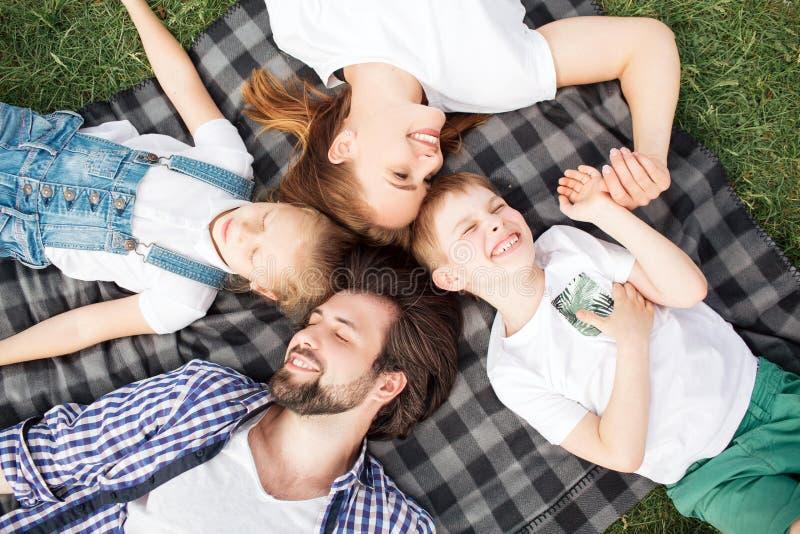 Herrliche Mitglieder der Familie liegen auf der Decke auf dem Gras Mann betrachtet Tochter Frau betrachtet Sohn stockfotos