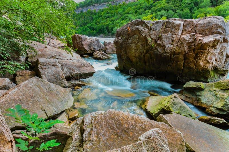 Herrliche Naturlandschaftsansicht von rauschender Fluss Niagara- Fallssteiler böschung mit großen Felsen und Steinhintergrund stockfotografie