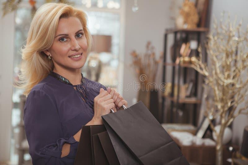 Herrliche reife Frau, die zu Hause Dekorspeicher kauft lizenzfreie stockfotos