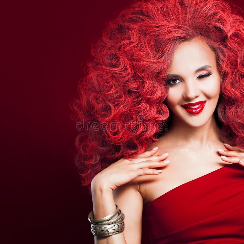 Herrliche rothaarige Mädchen Winks Junge Frau in der roten totalart stockbilder