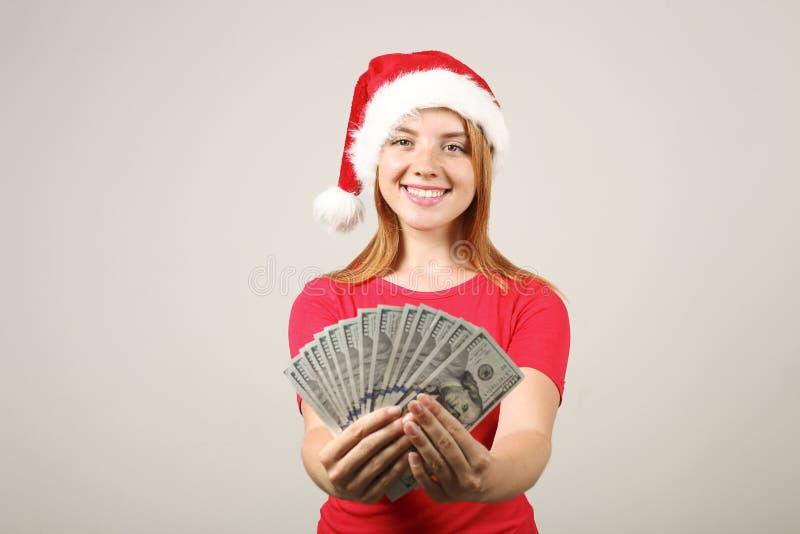 Herrliche Rothaarige weiblicher tragender Sankt-` s Hut mit dem Knall-pom, Winterfeiertagefeiertage feiernd stockbilder