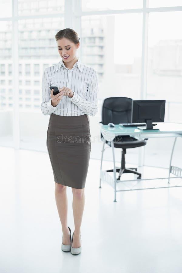 Herrliche ruhige Geschäftsfrau, die in ihrem Büro unter Verwendung ihres Smartphone steht stockfotografie