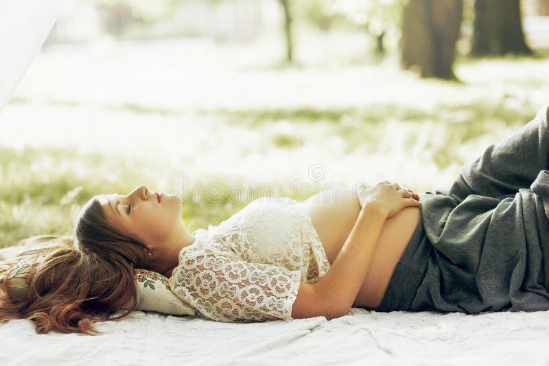 Herrliche schwangere Frau, die im sonnigen Park, ihren Bauch halten stillsteht lizenzfreie stockbilder