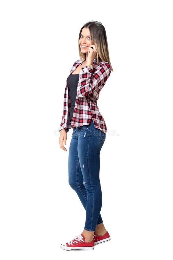 Herrliche stilvolle Straßenartfrau, die am Telefon lächelt an der Kamera spricht lizenzfreie stockfotografie