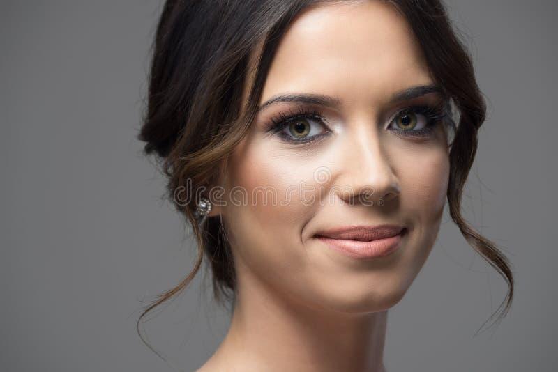 Herrlicher Abschluss herauf Porträt des Gesichtes der jungen Frau mit der Brötchenfrisur, die an der Kamera lächelt stockbilder
