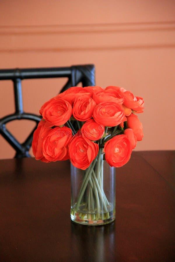 Herrlicher Blumenstrauß von hellen rot-orange Blumen im einfachen Vase auf Tabelle stockbild