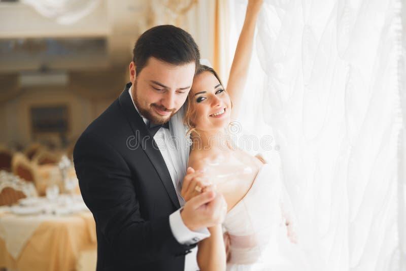 Herrlicher Bräutigam, der leicht stilvolle Braut umarmt Sinnlicher Moment von Luxushochzeitspaaren lizenzfreies stockfoto