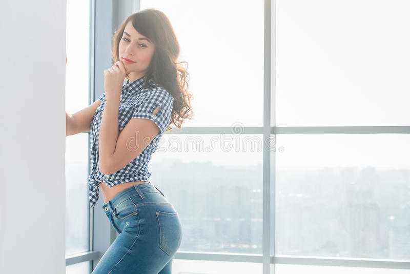 Herrlicher Brunette mit dem perfekten dünnen Körper, der, ihren Körper, tragendes kariertes Hemd und Blue Jeans verbiegend aufwir lizenzfreie stockfotos