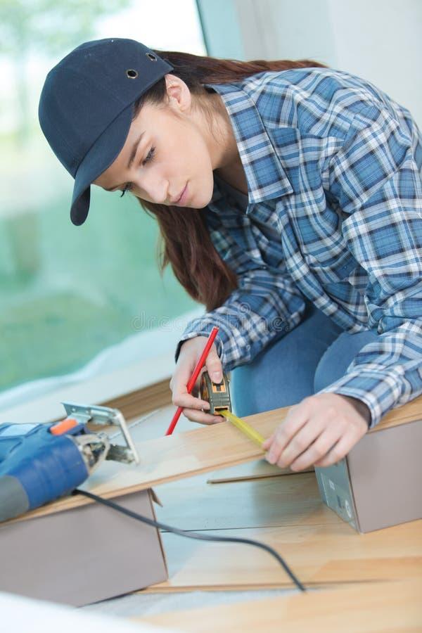 Herrlicher junger weiblicher Tischler, der Holzbearbeitung in der Werkstatt tut stockbild