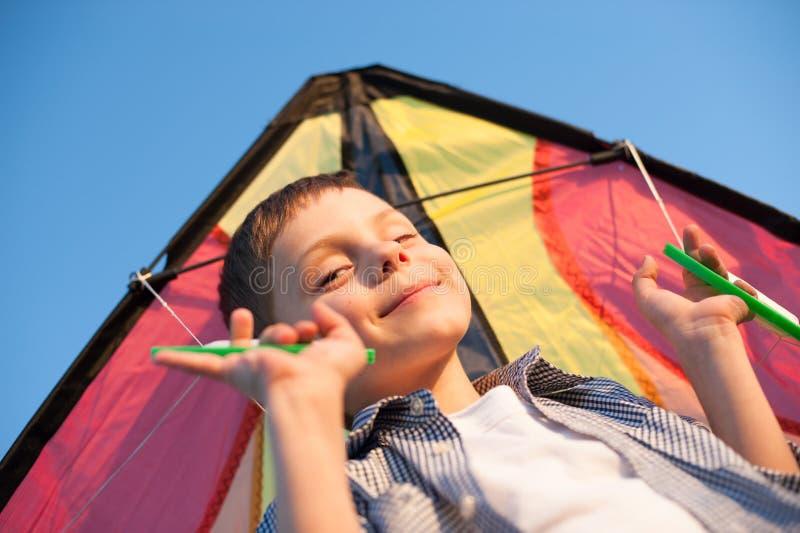 Herrlicher kleiner Junge mit buntem Drachen hinter Schultern auf Hintergrund des blauen Himmels lizenzfreie stockfotografie