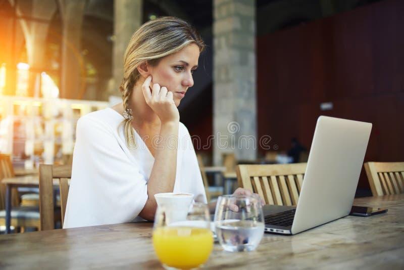 Herrlicher weiblicher Freiberufler, der Netzbuch für Fernjob beim Sitzen im modernen Caféstangeninnenraum verwendet lizenzfreies stockfoto