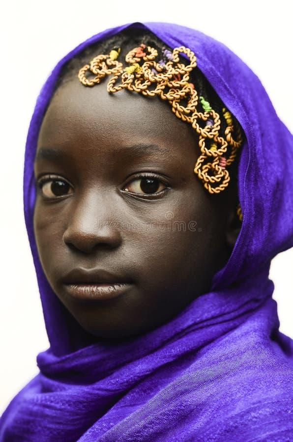 Herrliches afrikanisches Schulmädchen, das draußen mit Violet Head S aufwirft lizenzfreies stockbild